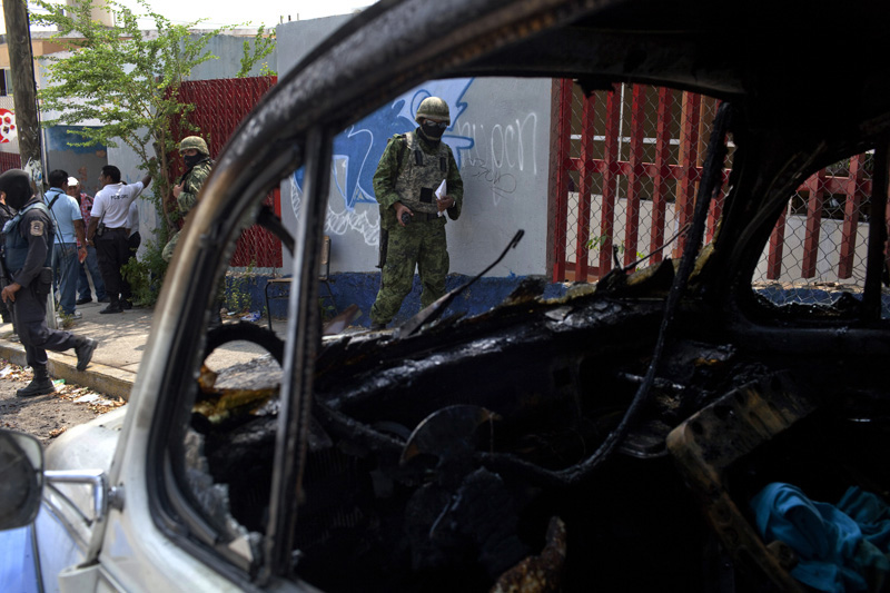 Policemen and military check the scene where apparently a driver was shot and then burnt inside his car, Acapulco, Mexico