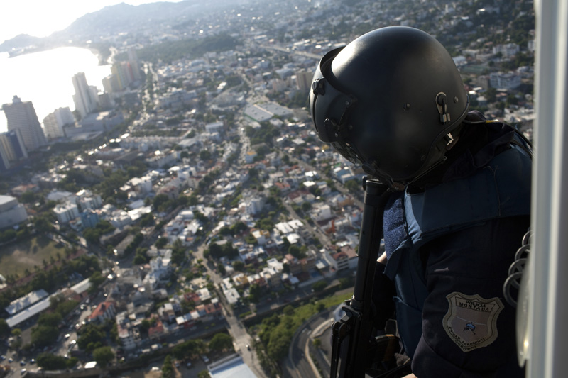 A state police man patrols the city from an helicopter, Acapulco, Mexico