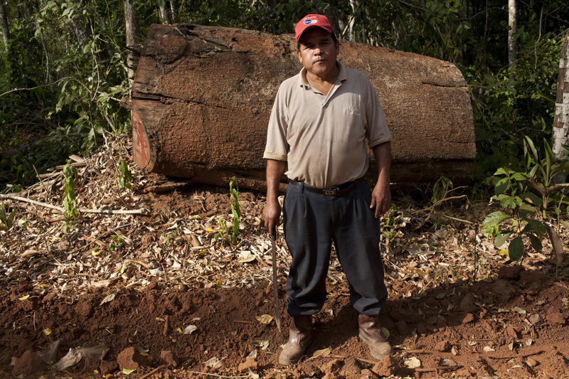 Truck driver German Guzman stands near the camp he lives on for months at a time while he works transporting logs to the town of Ascencion de Guarayos.