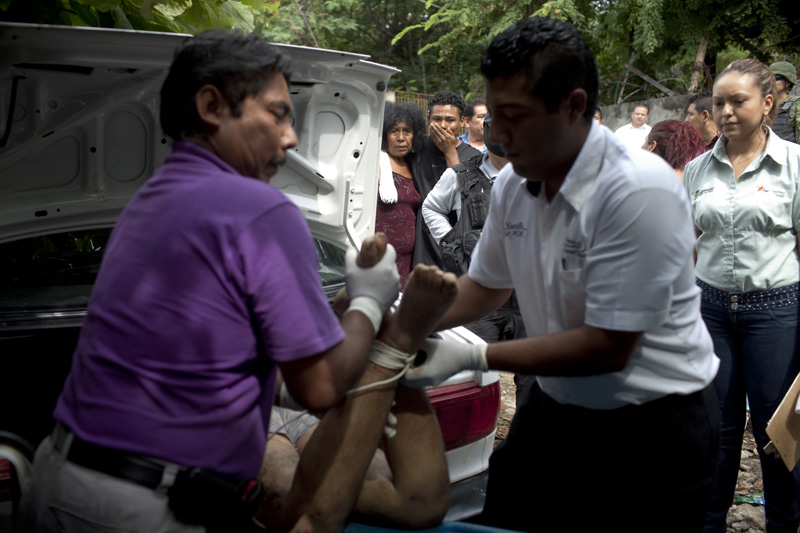 Forensic examiners pull two bodies out of a car, Acapulco, Mexico