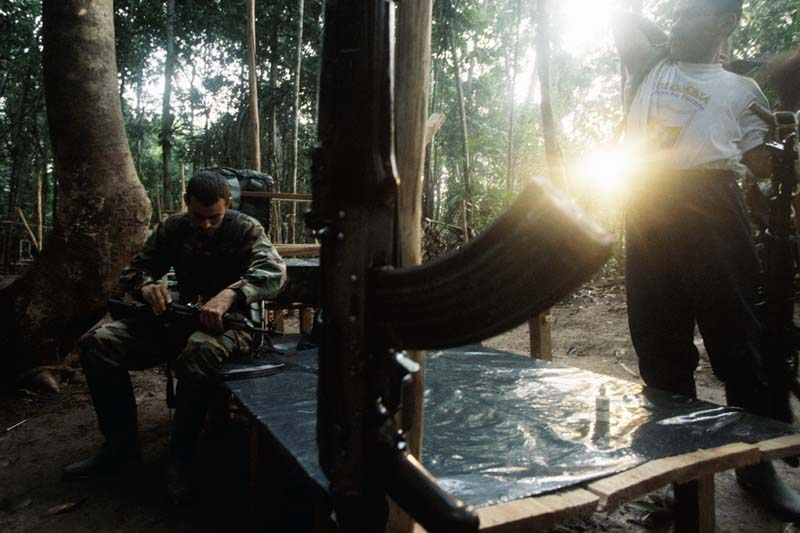 Early morning finds FARC guerrillas packing up a camp shrouded by tress, Colombia