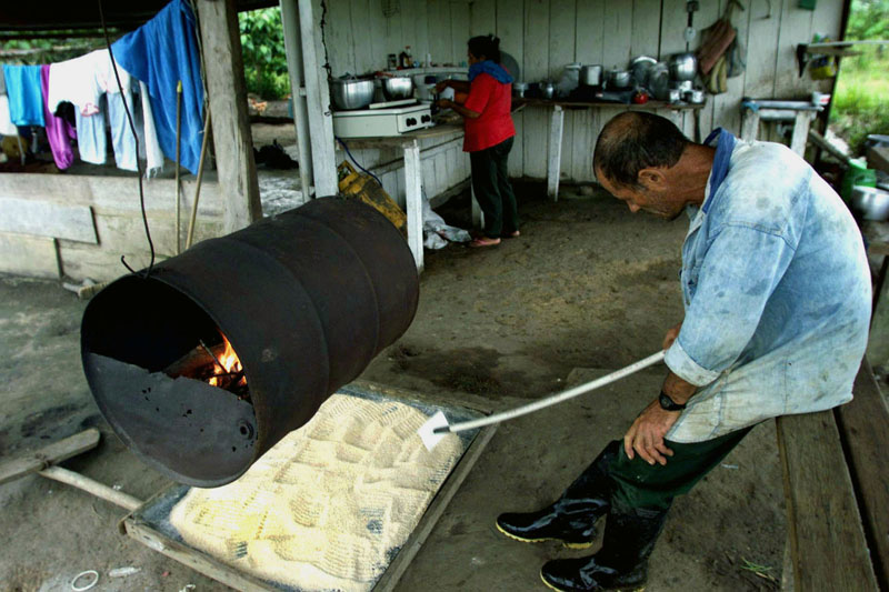 A farmer tends a batch of cocaine base under a heater as his wife brews coffee in the kitchen, La Playa, Colombia