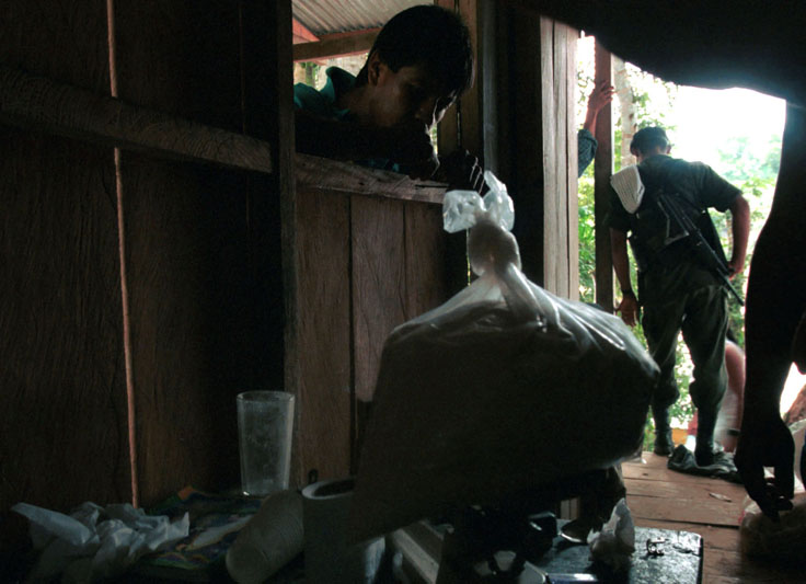 A FARC guerrilla stands by for security while a dealer weighs about a kilo of base in a shack across the river from Peñas Coloradas, Colombia