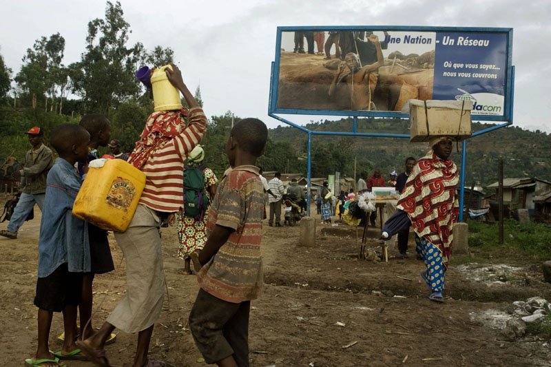 People walk on front of a billboard that depicts a miner digging for minerals while on a mobile phone, Bukavu, DR Congo