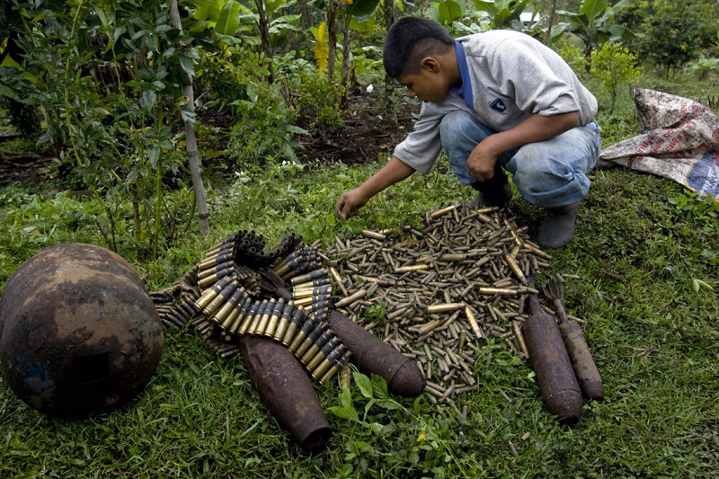 A youngster plays with ammunition left behind by the Colombian army and FARC guerrillas, Cauca, Colombia