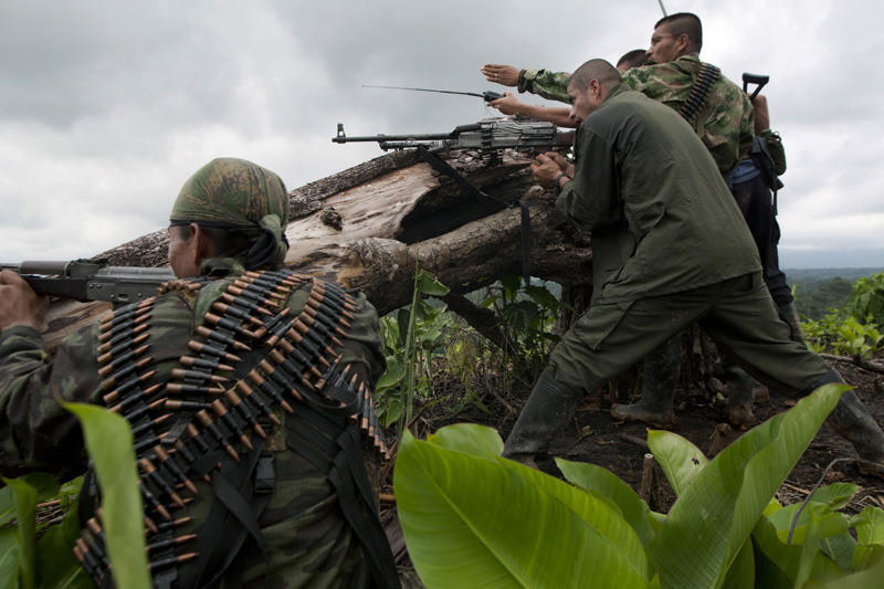 Revolutionary Armed Forces of Colombia, FARC, guerrillas shoot towards a position where colombian soldiers take cover in the mountains of Meta, Colombia