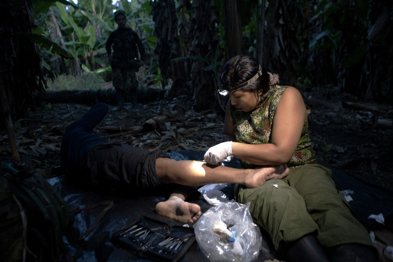 A Revolutionary Armed Forces of Colombia, FARC, nurse tries to get a bullet out of a guerrilla wounded during a shoot out with colombian soldiers in the mountains of Meta, Colombia