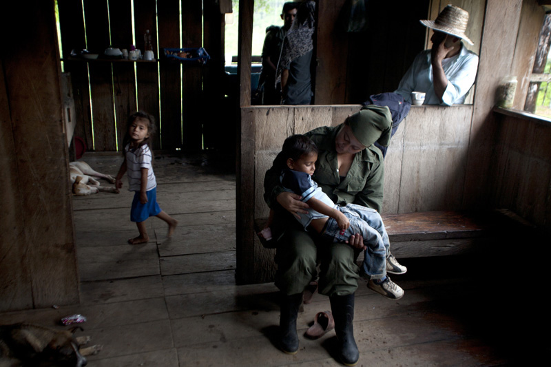 A Revolutionary Armed Forces of Colombia, FARC, guerrilla dentist talks to a child in the mountains of Meta, Colombia