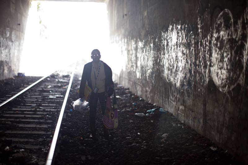 Carmen, a harm reduction program volunteer walks inside a tunnel know to be home of drug users in the South Bronx, NY, USA