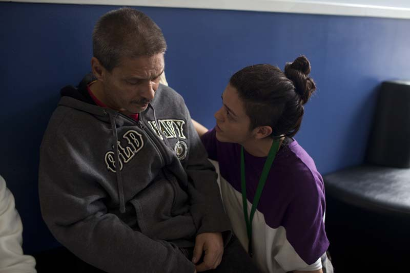 A harm reduction program worker comforts a man apparently suffering from a drugs overdose, NY, USA