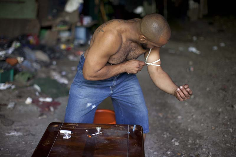 A drug user tightens up his arm to shoot himself with a heroin dose under a bridge in the South Bronx, NY, USA