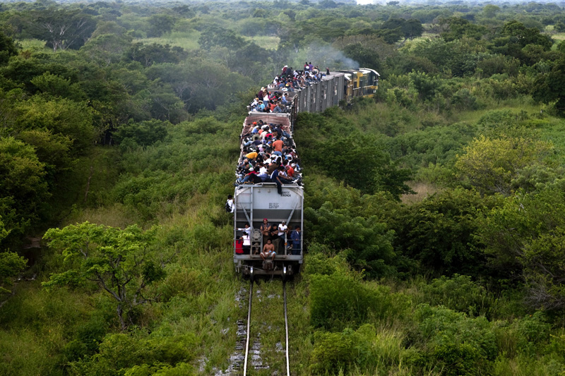 Illegal immigrants ride a cargo train towards the city of Ixtepec, Mexico