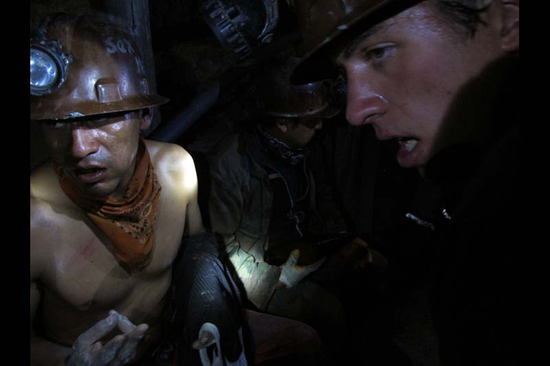 "British tourist Charles Newman is shown with miners deep inside a suffocating cavern in the Rich Mountain in Potosi, Bolivia. ""I thought the working conditions were pretty shocking, coming from Europe,"" said Newman, a 19-year-old Briton. ""It's quite humbling, actually seeing what they do on a daily basis."""