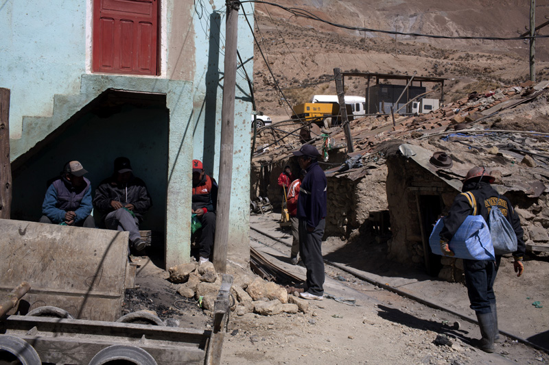 Outside the Candelaria mine on the Rich Mountain, miners relax before their next shift. For their troubles, most earn a paltry $14 a day, even as a commodities boom is generating far more earnings than in the past.