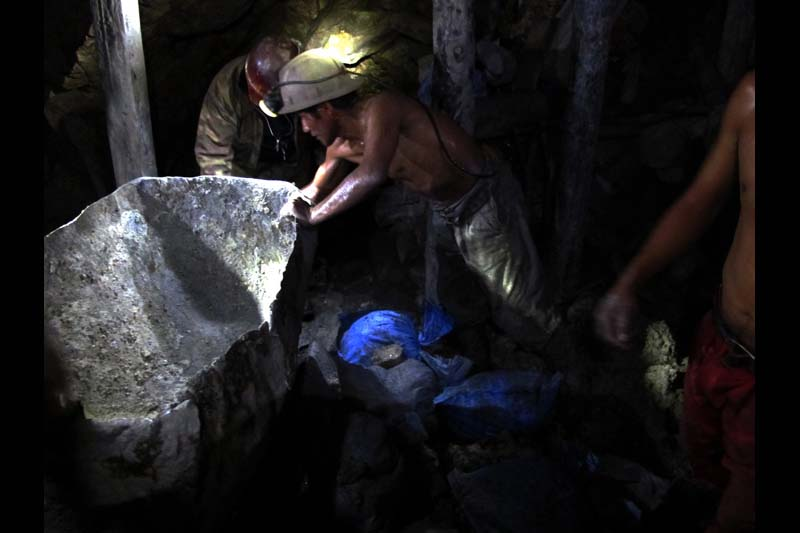 Miners fill and empty rail cars inside the Rich Mountain in Potosi, Bolivia.