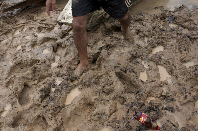 A porter walks in the mud in the port of Julio Cruz, Colombia, June 14, 2013. The port, located on a tributary to the Inirida river is used to download illegal tungsten from a mine controlled by Revolutionary Armed Forces of Colombia, FARC, guerrillas in the Inirida river.