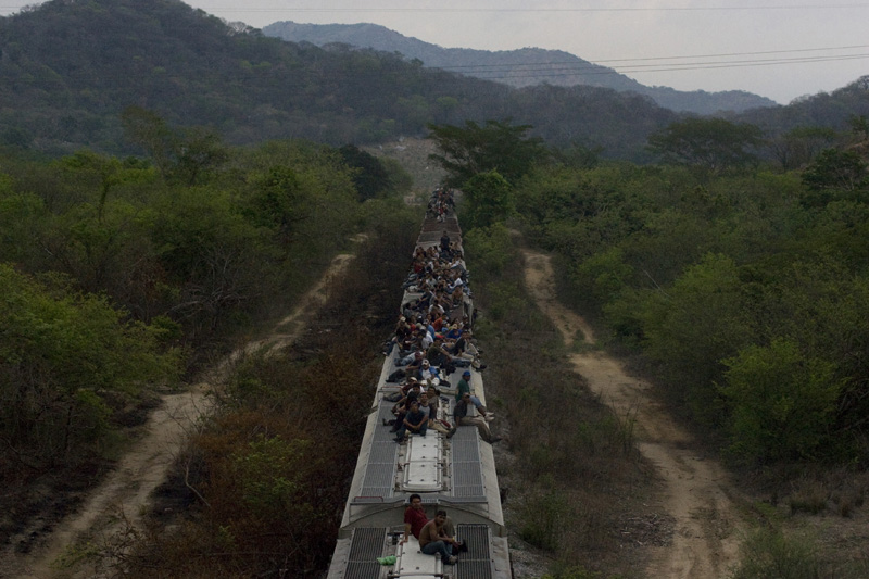 Latin American migrants riding a cargo train towards the northern city of IXtepec. Oaxaca, Mexico