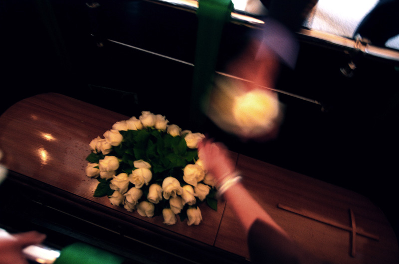 Some people grab roses from my father's casket before loosing sight of it, Santiago, Chile