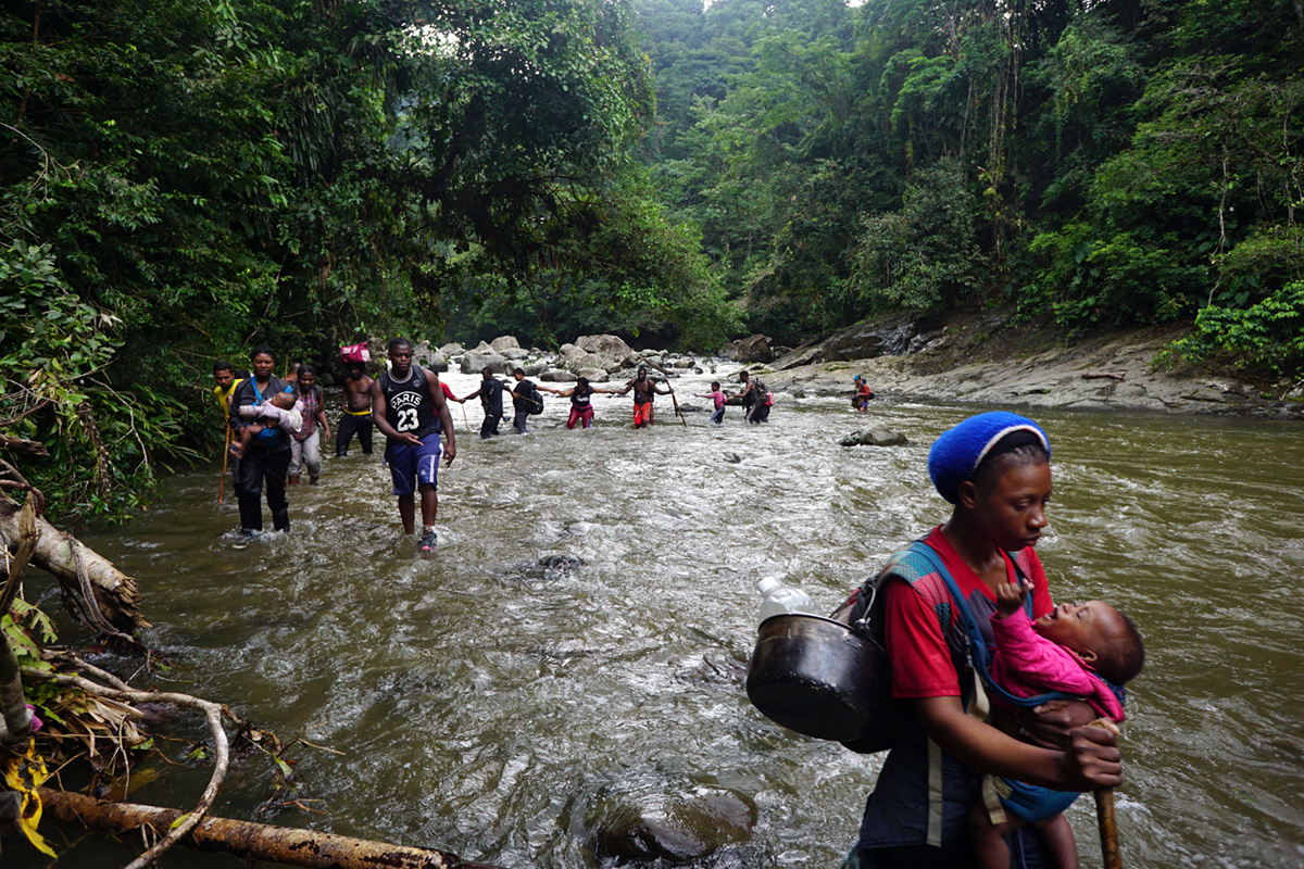Haitian immigrants walk along the Parraganti river in Panama, 2019.