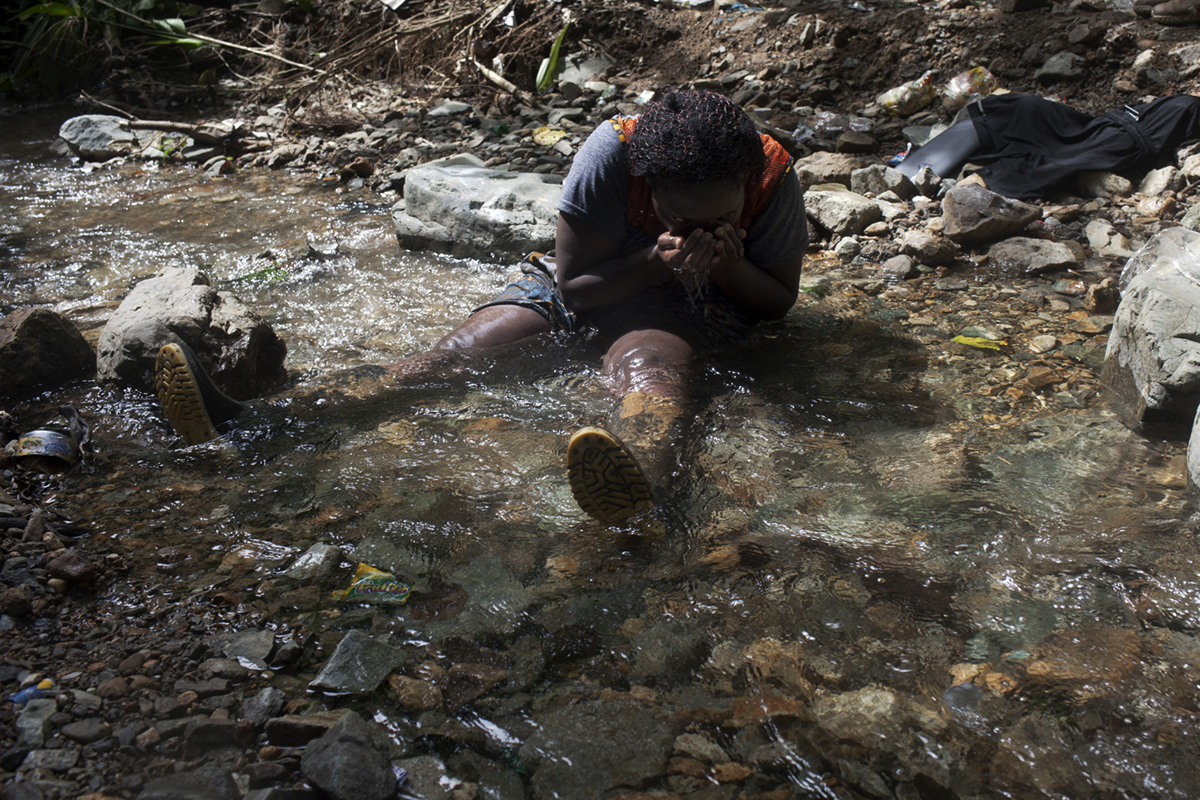 Weary and thirsty, Belinda, an immigrant from Cameroon who plans to live in Mexico city and wishes to bring along her three children and mother once she finds a job, drinks water from the Membrillo stream in the Darien gap after climbing up and down a mountain for six hours without the liquid, Panama, 2018.