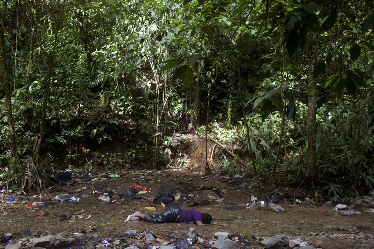Jolie, an immigrant from Cameroon, lies on the Membrillo stream after climbing up and down a mountain for six hours without water, Darien gap, Panama, 2018.