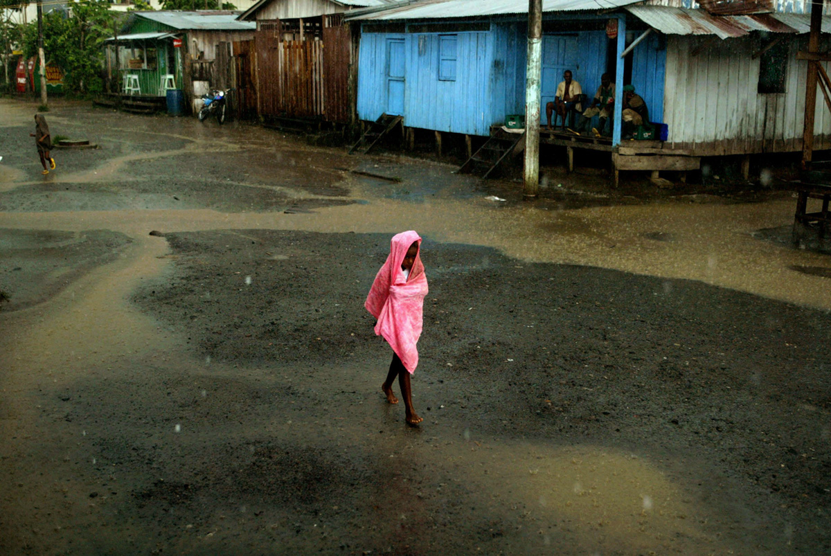 A girl walks under the rain in the town of Riosucio, Colombia, 2005.